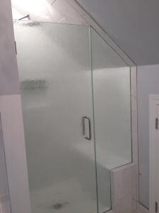 HG frameless door with inline notched panel, with clipped corner hinges, C-Pull, buried in tile